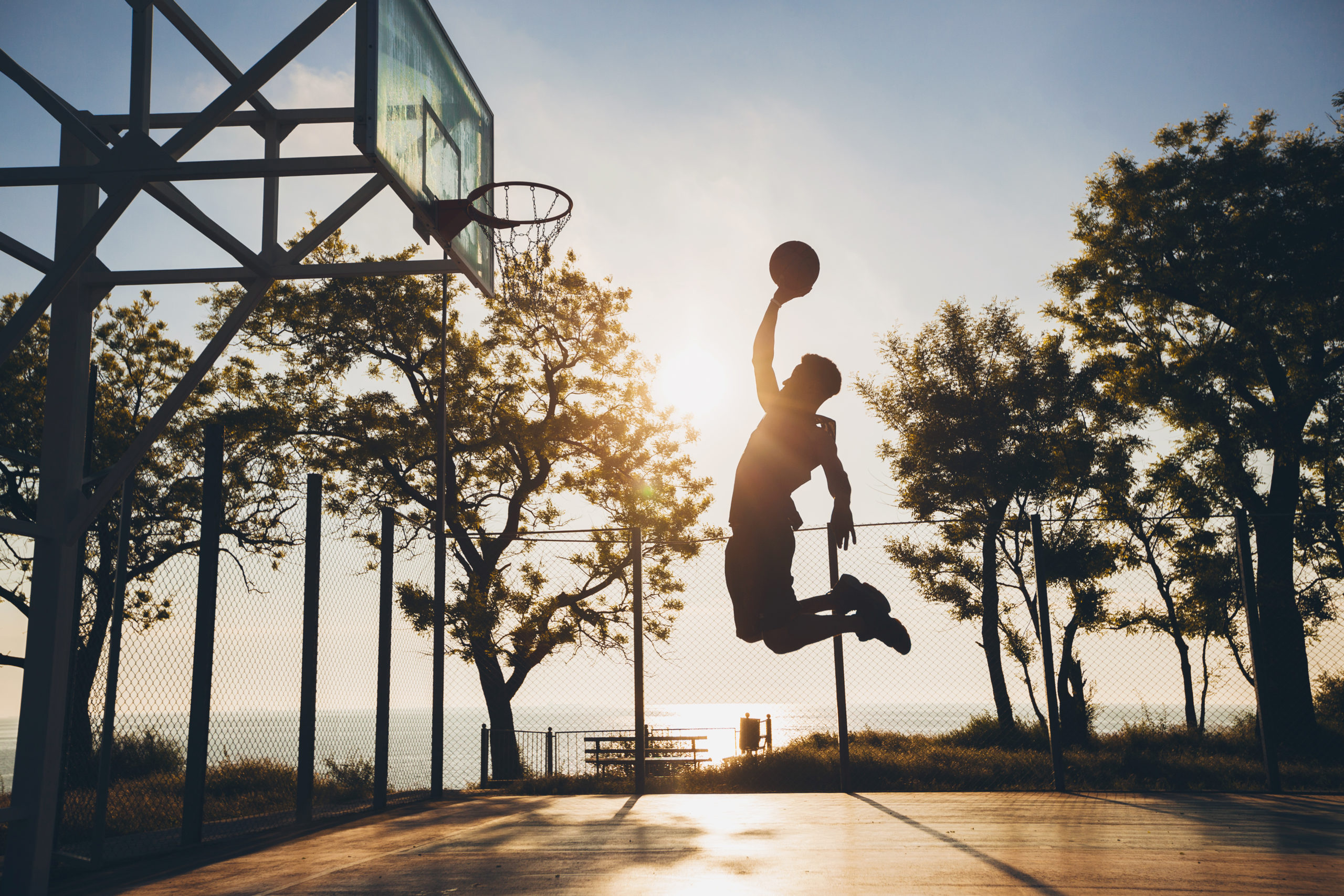 black man doing sports, playing basketball on sunrise, jumping silhouette
